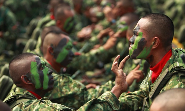 Indonesia's Airborne 328 soldiers help one another apply camouflage paint on their faces before a ceremony to mark the 67th anniversary of the Indonesian National Military at the tarmac of Halim Perdanakusuma airport in Jakarta.