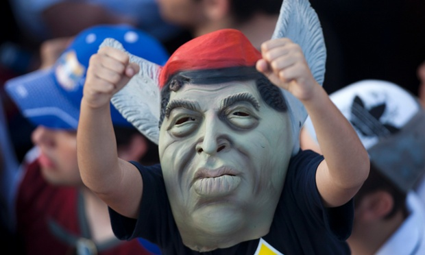 A supporter of the Venezuela's opposition presidential candidate Henrique Capriles wears a mask depicting Venezuela's President Hugo Chavez during a campaign rally in Barquisimeto.