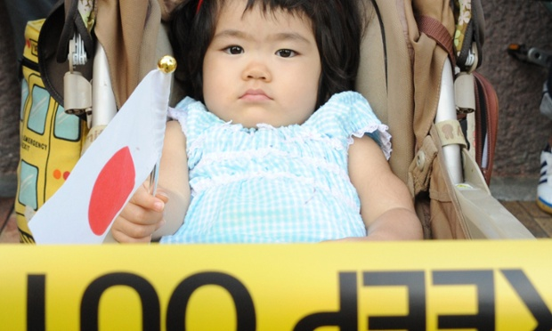 A little girl on a baby buggy holds a national flag as some 300 Japanese nationalists gather for an anti-China rally in Tokyo.