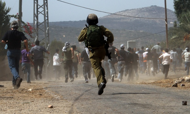 Israeli soldier chases masked Palestinian protesters during a protest against the Jewish settlement of Qadomem, near Nablus, West Bank.