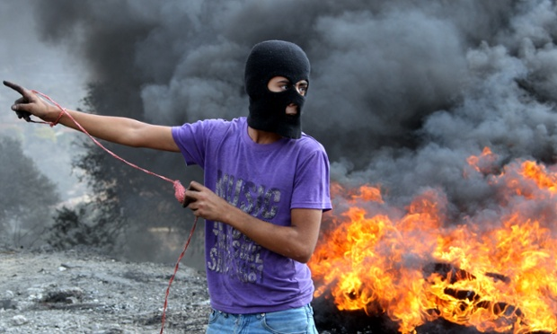 A masked Palestinian protester prepares to throw a stone towards Israeli soldiers