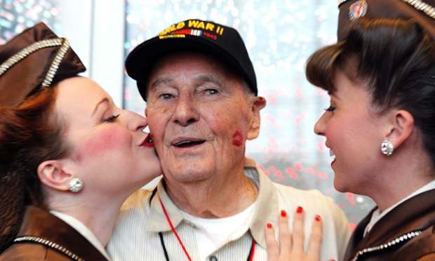 Thank you very much: Erwin Johnson a survivor of a WWII prison camp, reacts as he gets kissed on the cheeks from members of the 'The Victory Belles,' at the National World War II Museum in New Orleans.