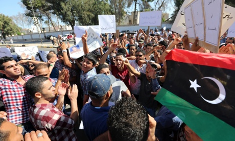 Libyan protesters from the city of Bani Walid shout slogans during a protest outside the National Congress in Tripoli on Sunday against the decision of the National Congress besieging their city. Libyan efforts to arrest the killers of a man credited with capturing Muammar Ghaddafi have turned into a siege of the city of Bani Walid.