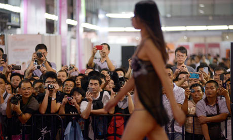 Chinese sex fair catwalk Men photograph semi-clad models on a catwalk at the ...