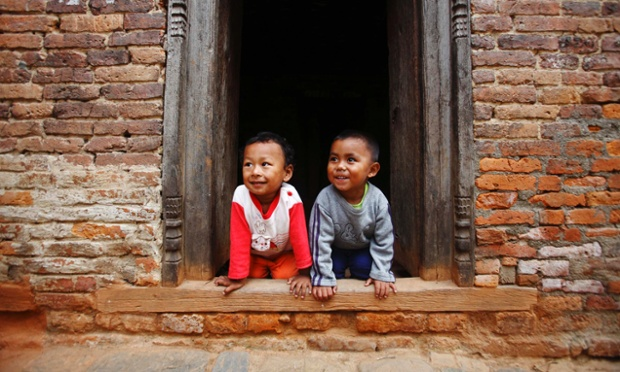 Boys smile while looking towards their mother at Khokana in Lalitpur, Nepal.