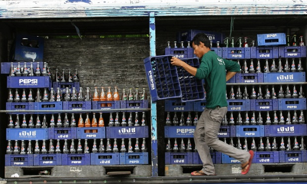 A Thai worker climbs on a truck while arranging crates of soft drinks before their delivery in Bangkok, Thailand.