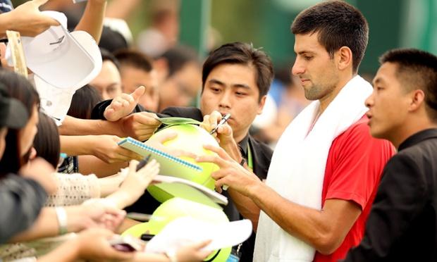 Novak Djokovic of Serbia signs autographs at the Qi Zhong Tennis Centre.