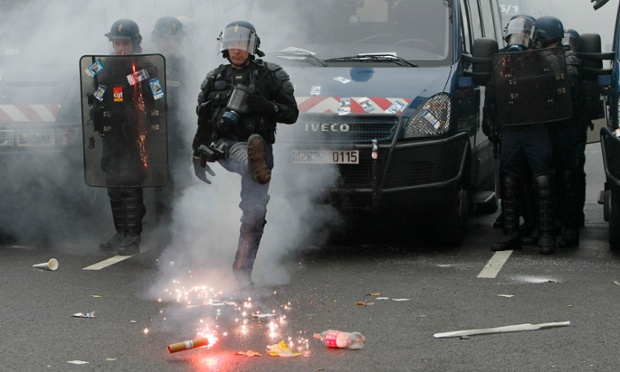 A French riot gendarme kicks a safety flare during a demonstration by union members in Paris.