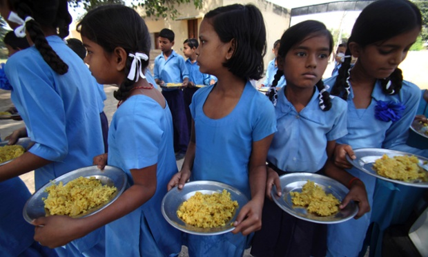 Indian schoolchildren receive a free midday meal at a government school in Jammu, India.