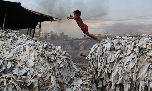 A child jumps on waste products that are used to make poultry feed as she plays in a tannery at Hazaribagh in Dhaka, Bangladesh.
