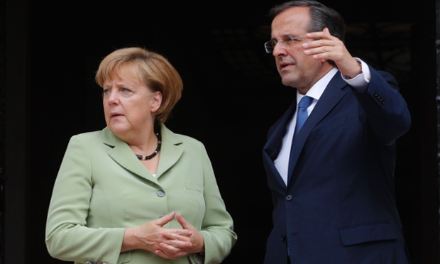 Just ignore them! Greece's PM Antonis Samaras greets Angela Merkel at the Maximos mansion in Athens.