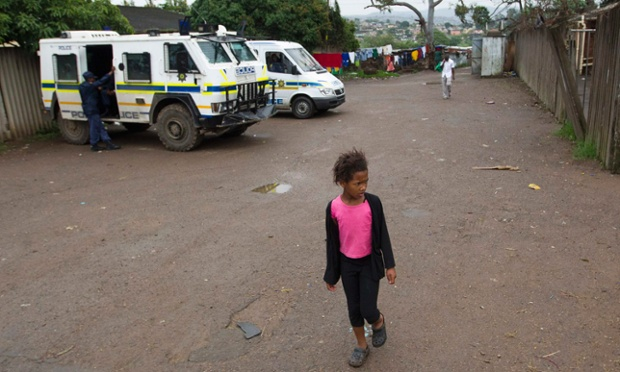 A young girl walks past police in KwaMashu after political violence erupted in the Durban township over the weekend, sparked by the abduction of Inkatha Freedom Party councillor Themba Xulu on Friday by men masquerading as police.