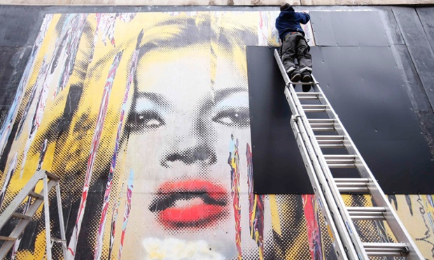A man removes covers from a piece of street art in central London.