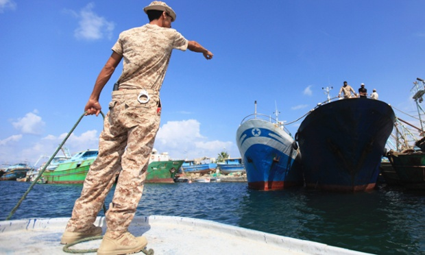 A member of the security forces points to the two Italian fishing boats 'Daniela' and 'Giulia' in the port of Benghazi, after they were seized about 50 miles east of Benghazi on Sunday night. The boats, with a crew of 14 people, were seized by Libyan authorities who said they were illegally fishing in Libyan waters.