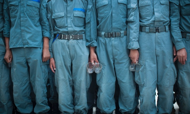 Tea time: Afghan National Police officers line up with their tea glasses before breakfast at the Police Academy in Kabul, Afghanistan. NATO defense leaders gathering in Brussels Tuesday are committed to the war in Afghanistan, according to U.S. and alliance officials, but there are growing signs that the Afghan political and military hostilities against the coalition are starting to wear on the coalition.