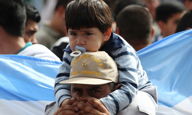 An officer from Argentina's Coast Guard carries his child on his shoulders during a protest outside his headquarters in Buenos Aires. Argentina's coast guard and military police held unprecedented wage protests, prompting the government to fire the heads of both services while Congress called for an orderly resolution of the dispute. Photograph: Enrique Marcarian/Reuters