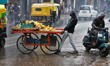 A fruit vendor struggles to cross a road with his cart in the rain in Bangalore, India.