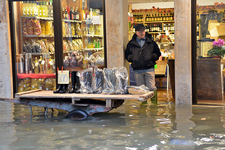 Venice floods: A shoe seller displays wellies outside his shop