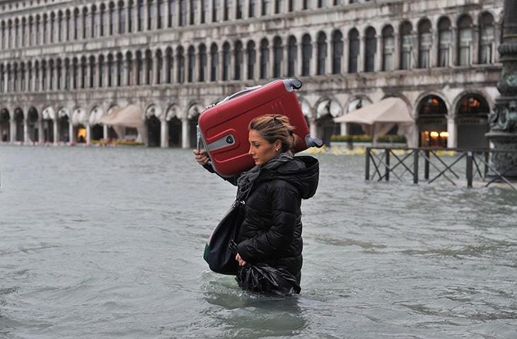 Venice floods: A tourist crosses flooded St Mark's Square