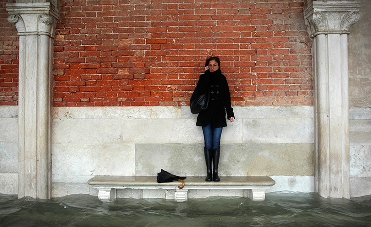 Venice floods: A woman stands on a bench above a flooded street