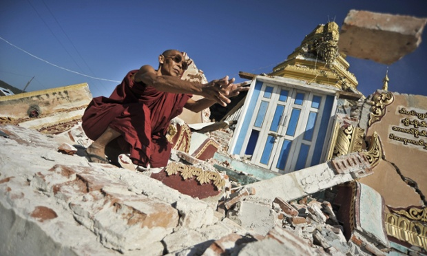 A monk clears debris from a destroyed Pagoda in Thabeikkyin, in Burma. According to reports, about a dozen people were killed by a 6.8 magnitude earthquake that shook the region two days ago.