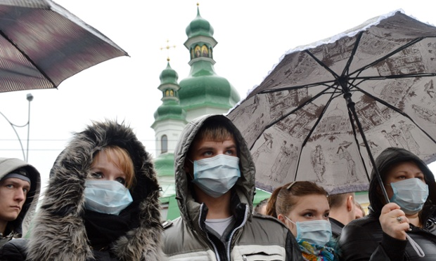 People in medical masks gather at the memorial monument to Aids victims in Kiev for a Ukraine to Quarantine! rally, demanding an increase in financing for treatment of epidemics