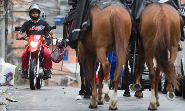 A motorcyclist drives along a road where mounted military police are patrolling the Paraisopolis slum in São Paulo, Brazil. At least 140 people have been murdered in South America's biggest city over the past two weeks in a wave of violence