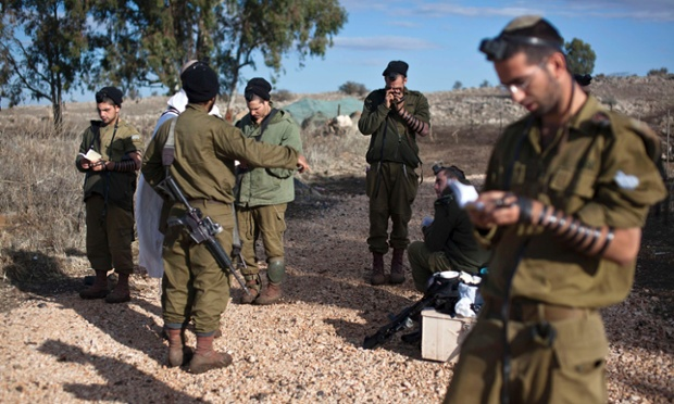 Israeli soldiers say their morning prayers close to the ceasefire line between Israel and Syria on the Israeli-occupied Golan Heights. Israel's army fired tank shells into Syria yesterday in response to a Syrian mortar shell that struck the Golan Heights, the Israeli military said in a statement.