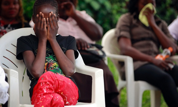 A young girl covers her face as she and other relatives wait at a mortuary where the bodies of police officers killed in an ambush were taken in Nairobi, Kenya. Armed cattle rustlers killed more than 40 police officers who were pursuing them, according to the local media, in the deadliest attack on the police in the country since its independence in 1963.
