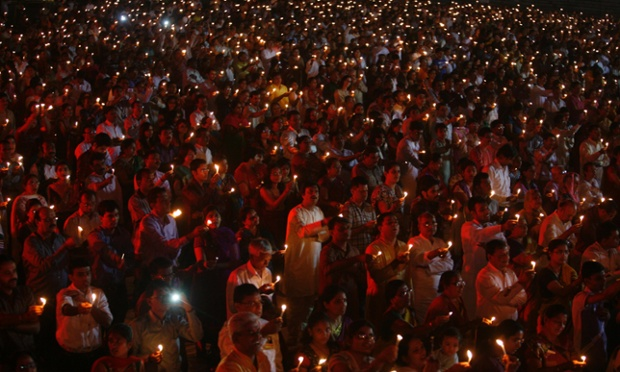 People hold candles during a mass gathering to celebrate Diwali, the Hindu festival of lights, in the western Indian city of Ahmedabad, India.