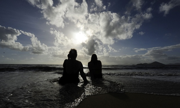 Spectators watch the solar eclipse while sitting in the surf in Palm Cove, Australia. Thousands of eclipse-watchers have gathered in part of North Queensland to enjoy the solar eclipse. Photograph: Ian Hitchcock/Getty Images