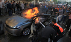 Palestinians put out the fire in Ahmed al-Jaabari's car following the Israeli airstrike
