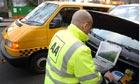 An AA patrolman studies a laptop under the open bonnet of a car, with his van parked beside it