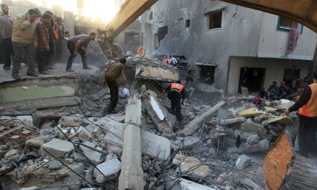 Palestinians search through the debris of the destroyed home of the al-Dallu family following an Israeli air strike in Gaza City.