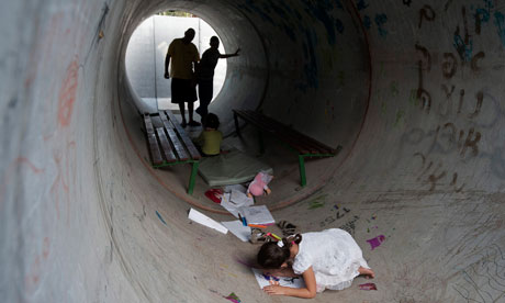 Citizens of Nitzan in southern Israel take cover in a concrete tube during a rocket attack from Gaza on 19 November