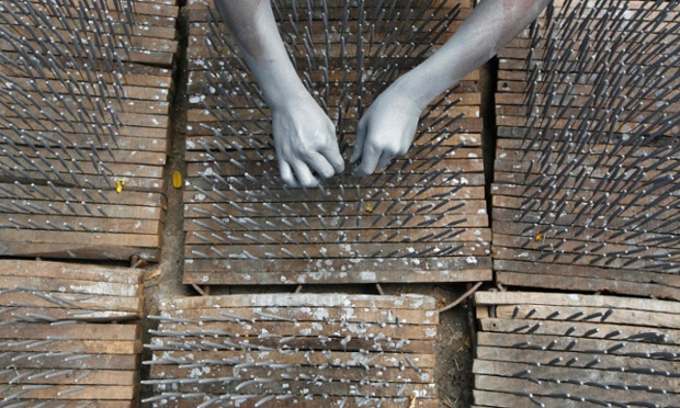 A worker's hands are covered with gunpowder as he makes fire crackers at a factory in Kolkata. Firecrackers are in great demand ahead of Diwali, the Hindu festival of lights, which will be celebrated across India on November 13. Photograph: Rupak De Chowdhuri/Reuters