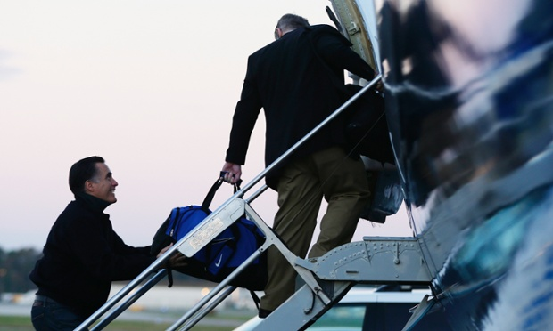 Mitt Romney smiles as he jokingly holds on to the bag of campaign strategist Stuart Stevens as they board their plane to clock-up a few more airmiles in Norfolk, Virginia early in the morning. Photograph: Charles Dharapak/AP