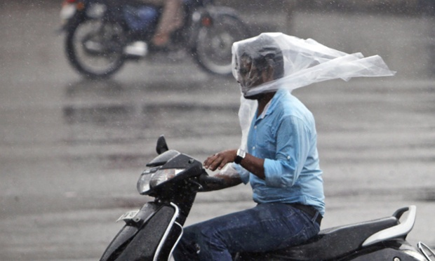 A rider uses a plastic sheet to cover his head while driving a scooter in the rain in Hyderabad, India. Photograph: Mahesh Kumar A/AP
