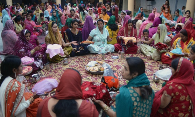 Indian women gather for a prayer event during the Karvachauth (Husband's Day) festival in Amritsar. Married women observe Karvachauth by fasting and offering prayers seeking welfare, prosperity, and longevity of their husbands. That's nice!