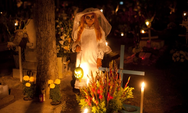 Frangerato Salvador, dressed as a Katarina, stands beside her brother's grave, marking the Day of the Dead holiday at the cemetery in San Gregorio, Mexico. The holiday honours the dead coinciding with All Saints Day and All Souls' Day.