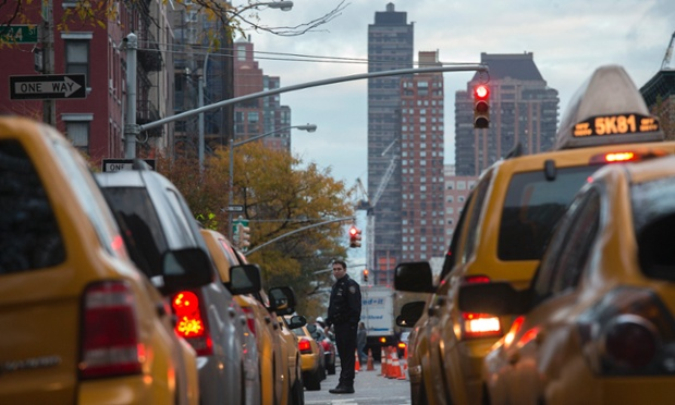 A policeman stands guard between lines of New York City yellow taxis and cabs waiting to get fuel from a gas station in Midtown Manhattan. A key pipeline delivering fuel into the storm-stricken New York area has resumed shipments and barge shipments were slowly returning to normal today.