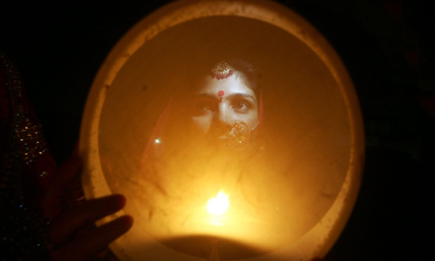An Indian married woman performs a traditional ritual as she visualizes the moon on the occasion of Karva Chauth festival in Jammu, the winter capital of Kashmir, India. On this day Hindu married women observe fast and pray for the longevity and well being of their husbands and break the fast only after sighting the moon.