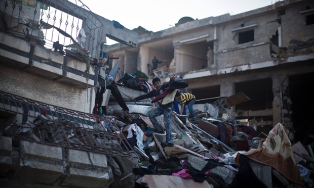 Palestinian children salvage belongings from a building destroyed in the conflict.