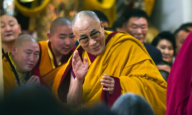 The Dalai Lama gives a cheery wave to devotees as he arrives to give a religious talk at the Tsuglakhang temple in Dharmsala, India.
