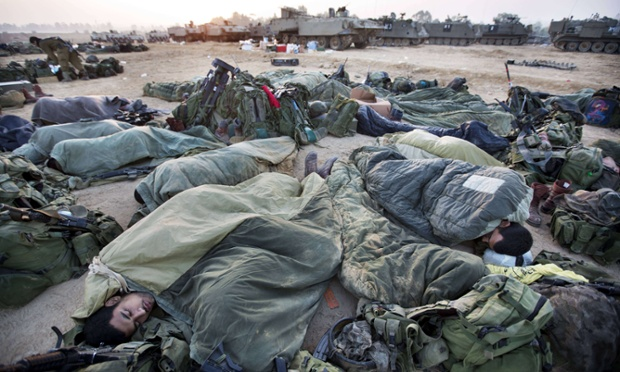 Israeli soldiers sleep near armoured personnel carriers at an Israeli army deployment area near the Israel-Gaza Strip border, as talks aimed at securing a deal between Israel and Gaza's Islamist Hamas rulers continue. Israel halted a threatened Gaza ground offensive to give truce talks a chance.