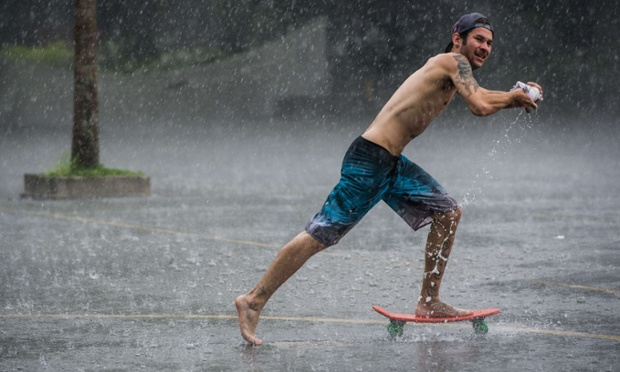 A man wrings his t-shirt as he skateboards in the rain at Ibirapuera park in Sao Paulo, Brazil. Photograph: Yasuyoshi Chiba/AFP/Getty Images