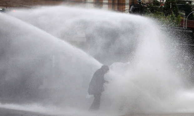 A riot police vehicle releases a jet of water on a fisherman during a protest against a new fisheries law proposed by the government in congress, in Valparaiso city, northwest of Santiago, Chile.