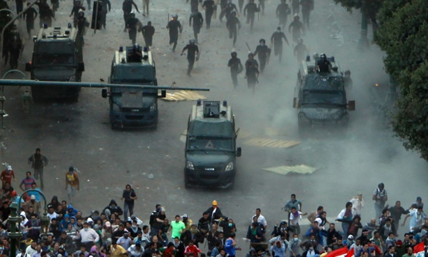 Protesters run from riot police during clashes at Tahrir square in Cairo, Egypt