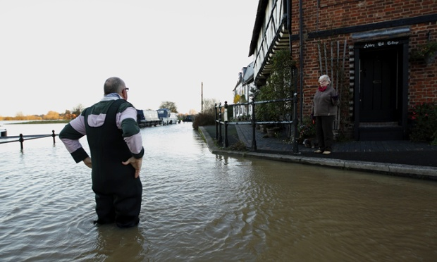 Unlucky Tewkesbury is up to its knees in it again. A man speaks with a passing woman as he stands in floodwaters in Tewkesbury town centre.