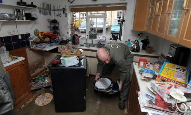 Oliver Smith clears his mother's home in Malmesbury after it was flooded over the weekend. Britain's beleaguered towns and villages were dealt a further blow today as more rain battered the country and 200,000 householders were warned they could lose their home insurance policies.